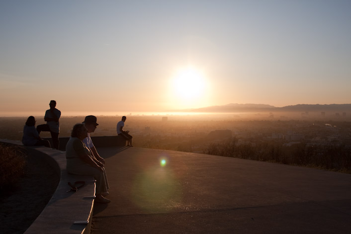 People rest and take in the sights from the overlook as the sun sets on a smoky LA Basin