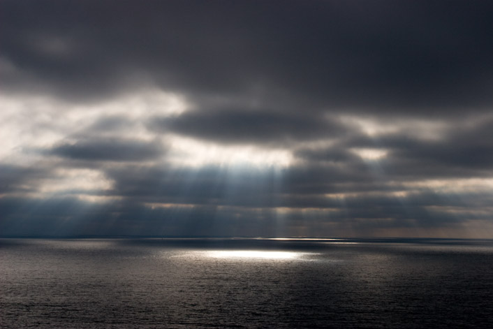 God rays shine from between the clouds over a dark Pacific